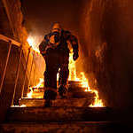 Back view of a firefighter going up the stairs of a burning building.