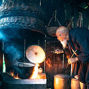 Old Chinese senior man cooking water in simple kitchen.