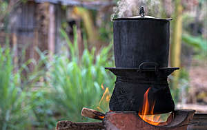 Black pot boiling for the rice cooker on the fired stove next to firewood pile.