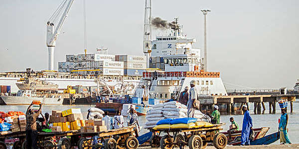 Men loading carts with goods off a ferry and a pirogue in The Gambia.