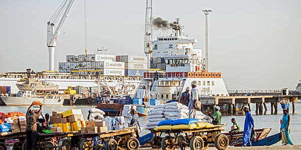 Des hommes chargeant une voiture avec d'autres marchandises depuis le ferry et la pirogue en Gambie.