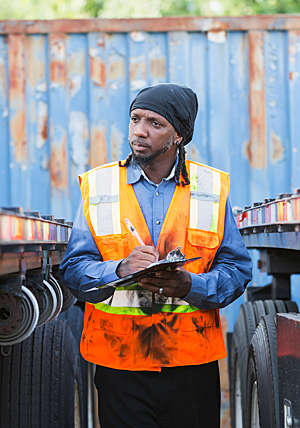 Man in safety vest stands between two semi-trucks taking notes.