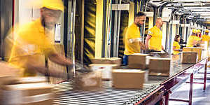 Workers sorting packages which are moving on a conveyor belt, in a distribution warehouse.