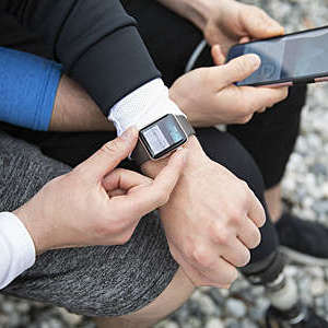 Overhead view gay couple preparing smart watch, checking fitness app on smart phone