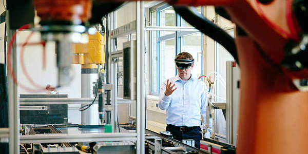 Engineer works with a HoLoLens headset to place a virtual robotic arm into the production line.