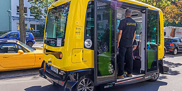Small self-driving yellow bus on the road in Berlin.