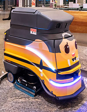 Robot cleaning vehicle with yellow body and cartoonish face photographed in Singapore's Changi Airport.