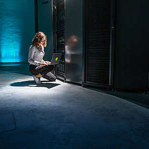 Female IT engineer using working on her laptop, in a server room.