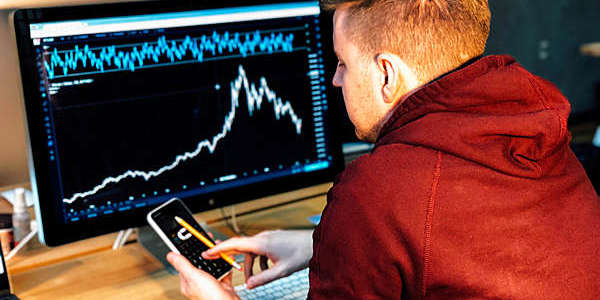 Man follows a stock chart on a computer screen while tapping away on his mobile phone.
