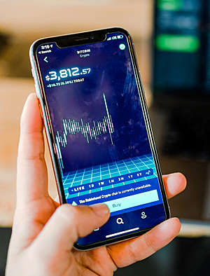 Close-up of hand on smartphone trading cryptocurrencies.