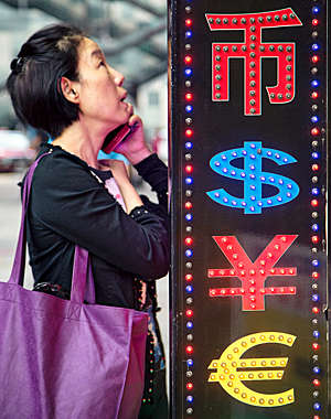 Asian woman talks on her smartphone next to a neon sign displaying currency codes.