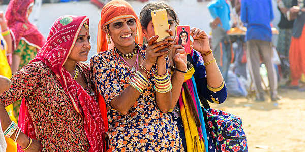 Three Indian women staring at a smartphone.