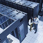 High-angle view of two technicians talking in a server room.
