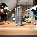 Two people work on a virtual 3D building using augmented reality glasses.