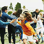 Young female soccer goalie high-fives parents on the sidelines after a soccer game.