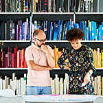 Close view of two colleagues absorbed in a discussion against a backdrop of colour-coordinated bookshelves.