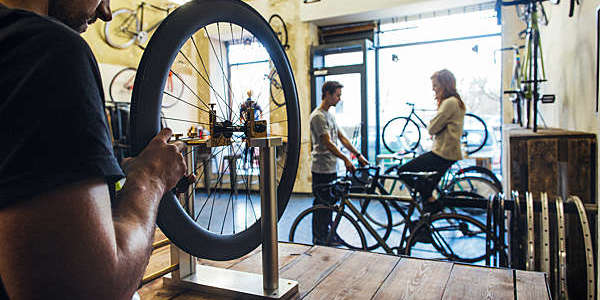Close shot of bicycle mechanic repairing a wheel while a salesman attends a client in the background.