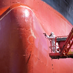 A worker spray painting the underside of a ship in dry dock.