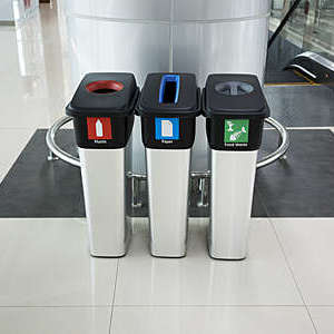 Colour-coded recycling bins inside an airport terminal.