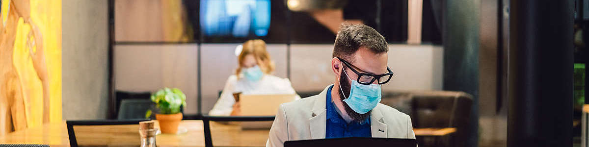 Employees wearing masks sit a safe distance apart in the office.