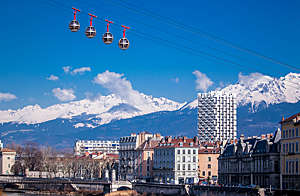 Four cable cars sail over the city of Grenoble against a blue sky and mountains.