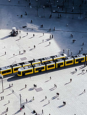 Aerial view of two yellow trams crossing on a main city square.