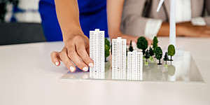 Architect woman's hand holding buildings models on a conference table.