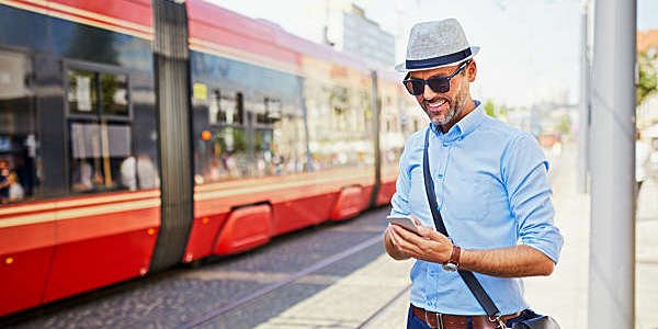 Tourist checks tram schedule on his smartphone as a red tram pulls up.
