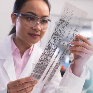 Female scientist examines a DNA profile in a laboratory.