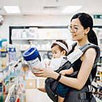 Mother carrying a baby girl in an infant carrier examines tubs of baby formula in a supermarket.