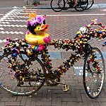 Section view of a bicycle decorated with garlands of plastic ducks and a yellow duck on the saddle on a street in Amsterdam, Holland