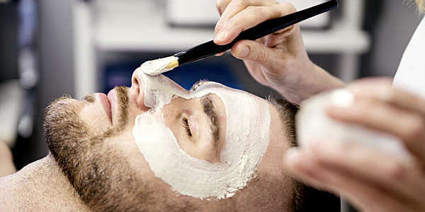 Young man receiving a facial treatment in a health beauty spa.