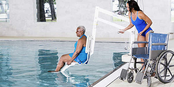 A physical therapist lowers a senior female patient into the pool using a spa lift.