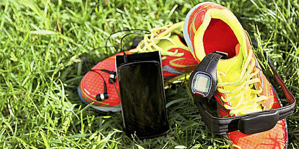 Black sports watch, smartphone and headphones placed on a pair of yellow and red sneakers on the grass.