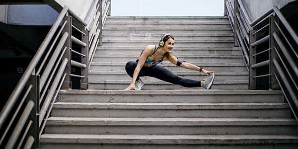 Young woman wearing headphones, crouched halfway up a flight of steps, performs stretching exercises before her run.