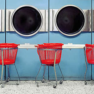 Public laundry area with a view on four empty washing mashing and three red emptied plastic baskets in between them.