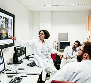 Female clinical registrar perched sideways on a desk discusses with two male colleagues a patient's test results displayed on a large screen.