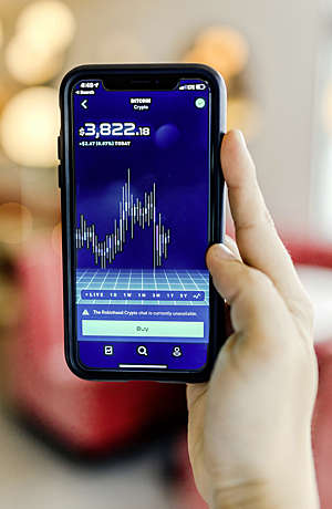 Hand holds a smartphone displaying the Bitcoin exchange rate.