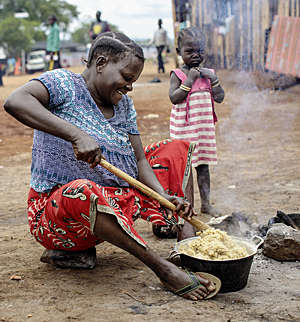 Refugee women from the Congo cooks food sitting on the ground at the Kyangwali Refugee Settlement in Uganda.
