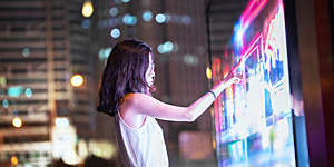 Young woman using a large interactive screen on a Shanghai street at night.