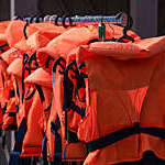 Vanishing perspective of orange lifejackets on black hangers.