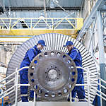 Two engineers in blue caps and overalls repair a steam turbine in a workshop.