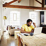 A guy wearing a yellow t-shirt works from home using his dining room table as a desk