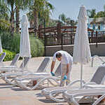 Hotel employee measuring social distancing between deck chairs by a hotel swimming pool.