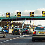 Cars queuing to pass through the barriers on a Toll road.