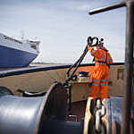 Tug worker in protective orange clothing holding a rope on deck.