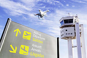 Drone flying low over an airport nearby a control tower, with departures/arrivals panel in the forefront.