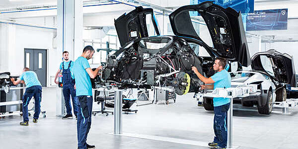 Two men from car manufacturers, working on the latest Concept-Two all-electric hyper car model.