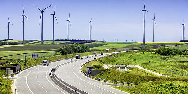 Highway running through green fields with wind turbines on the horizon.