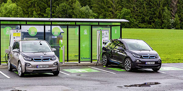 Two cars plugged into an electric vehicle charging station against the green backdrop of the Norwegian countryside.